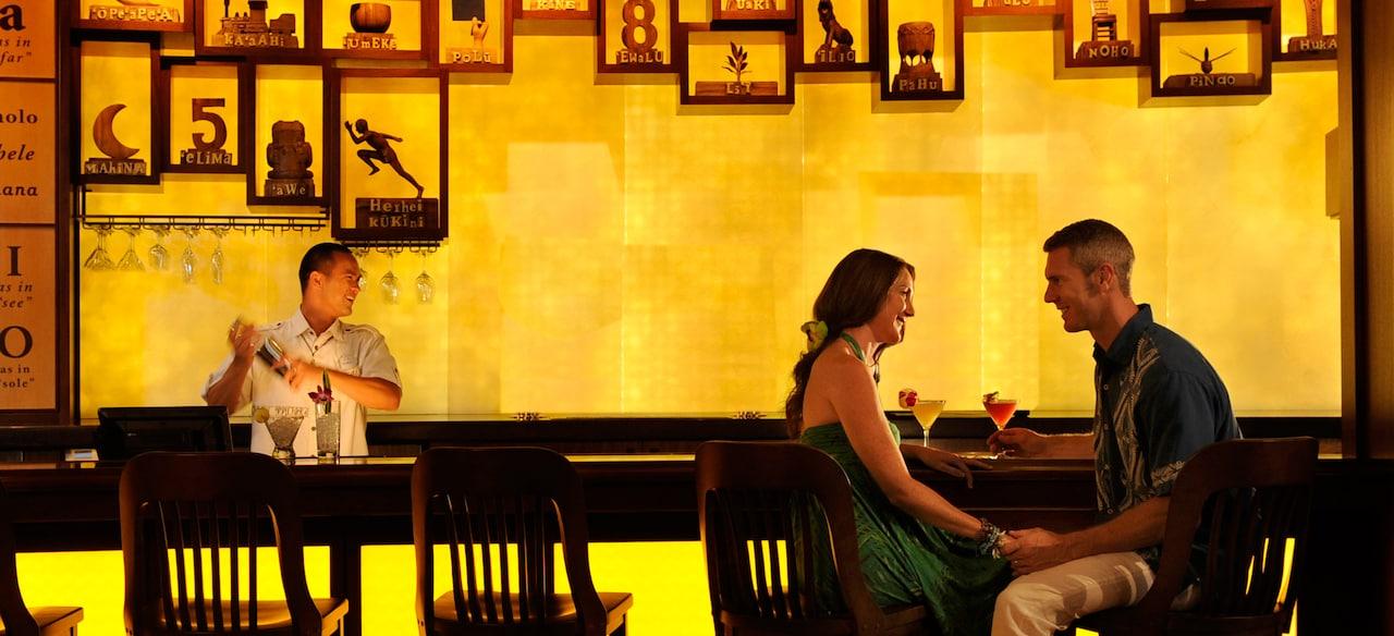 ロマンチックなひと時とトロピカルカクテルを楽しむカップルと、シェイカーでカクテルを作っているバーテンダー