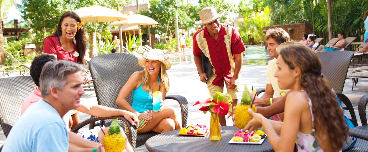 Two servers tend to 3 couples enjoying drinks and tropical fruit plates at a table near a pool