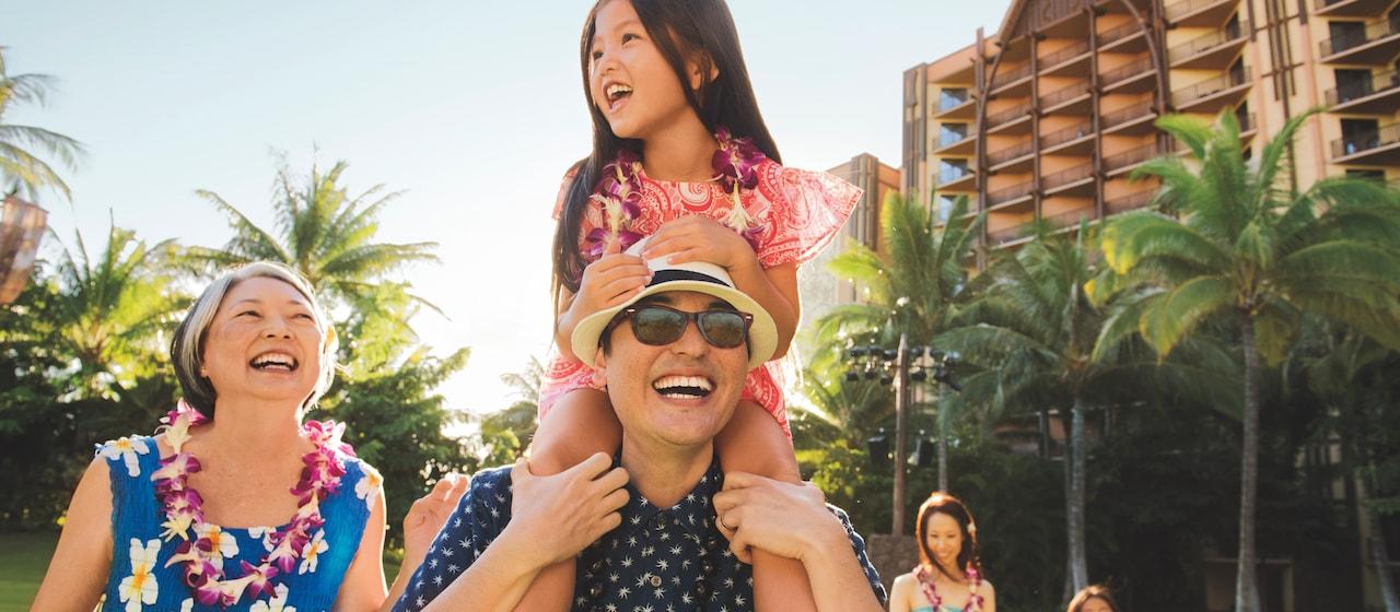幼い女の子を肩に乗せて歩くおじいさんと、横を歩くおばあさん。