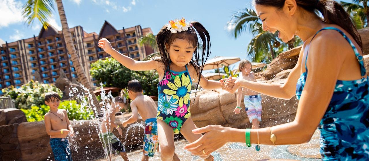ケイキ・コーヴの噴水で水遊びをする娘を笑顔で見ている母親