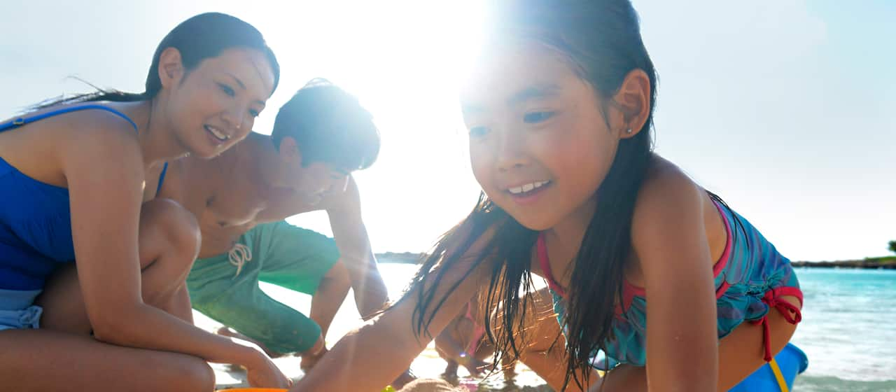 砂浜で遊ぶのを楽しんでいるヤングファミリー
