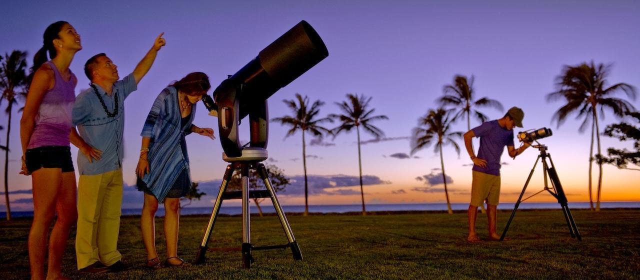 日の暮れた浜辺でアウラニのガイドの指し示す星を望遠鏡で覗く男女