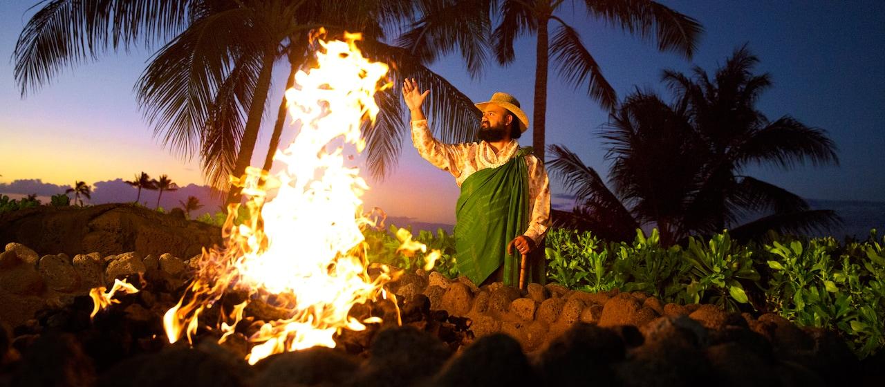日暮れ後に火の傍に立ち、アウラニの物語を語るアンクル