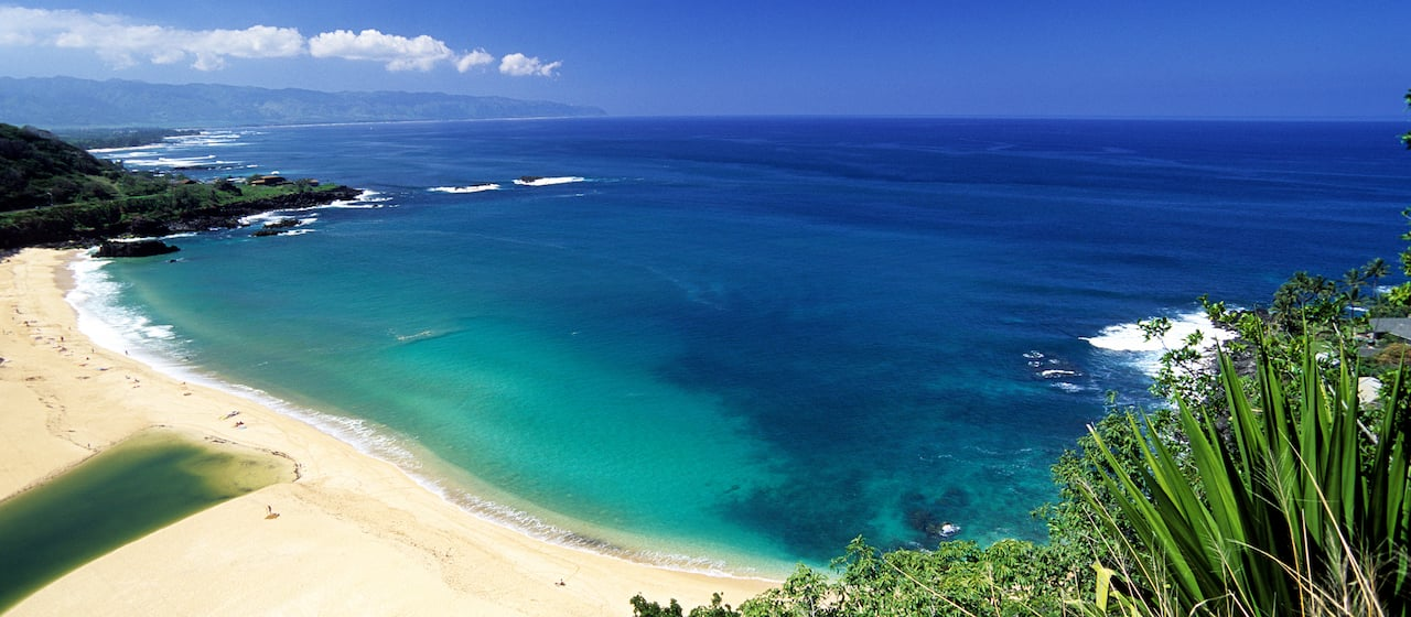 An aerial view of a beach in a cove on the North Shore of Oahu