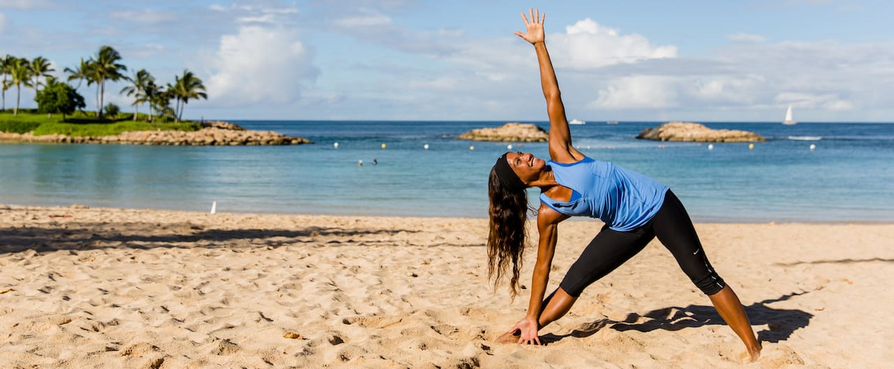 A woman on the beach in workout clothes stretches one arm to the sky and the other to the ground