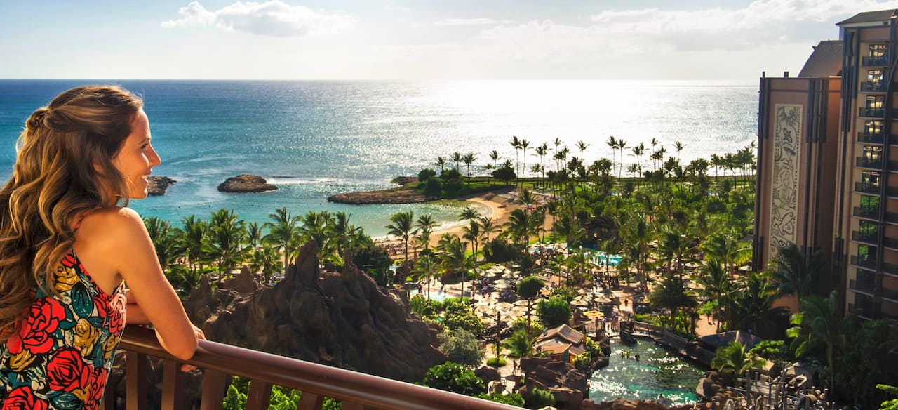 A woman stands at the balcony with an ocean view overlooking the Aulani grounds and pool area