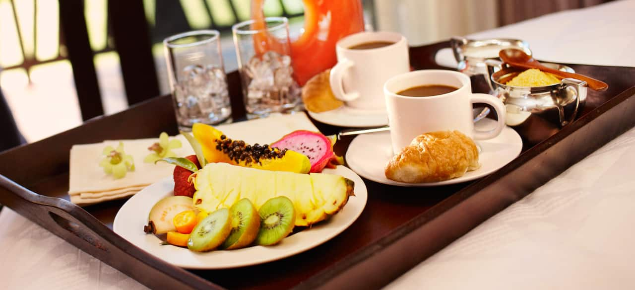 A room service tray holds a breakfast of tropical fruits, coffees, croissants and juice