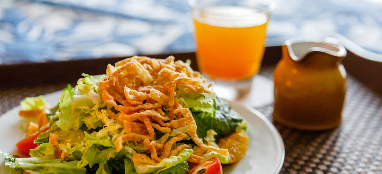 A room service tray holds a beverage and a heaping plate of salad greens topped by wonton strips