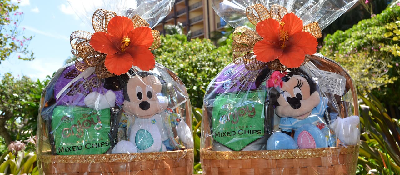 Packaged Hawaiian treats in 2 gift baskets featuring a plush of Mickey Mouse or Minnie Mouse