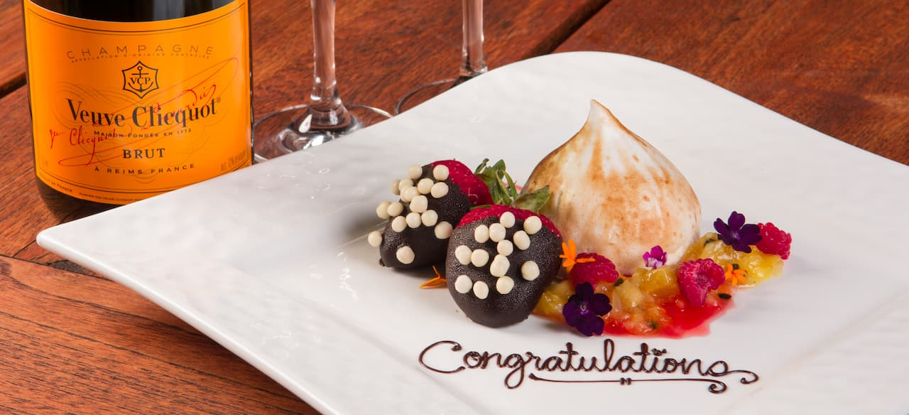 """Congratulations"" is written in chocolate on a plate of confections beside a bottle of champagne."
