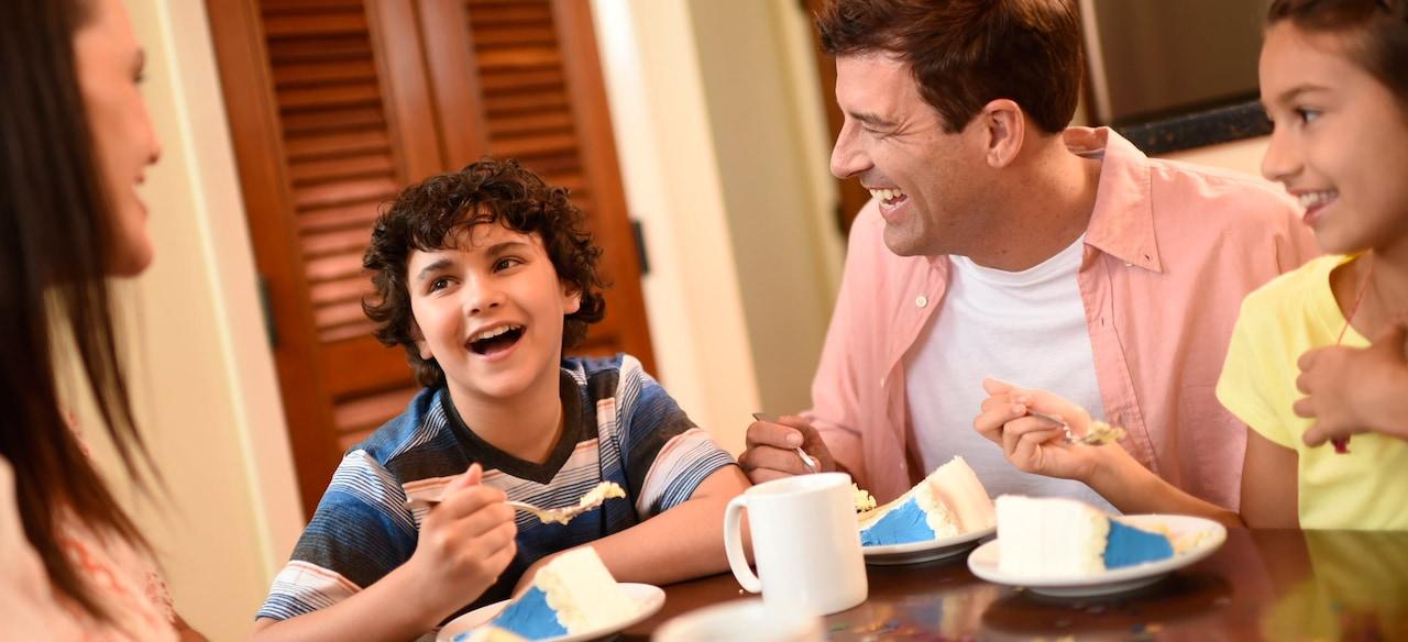 テーブルを囲んでケーキを食べながら談笑する 4 人のファミリー