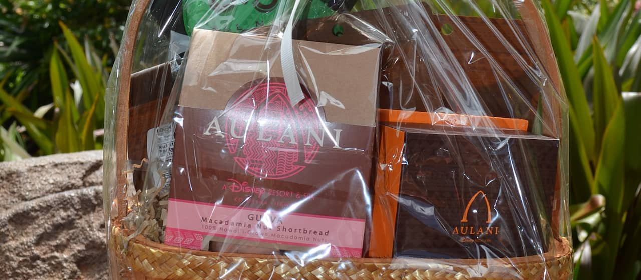 A gift basket of packaged tropical treats, topped with a flower