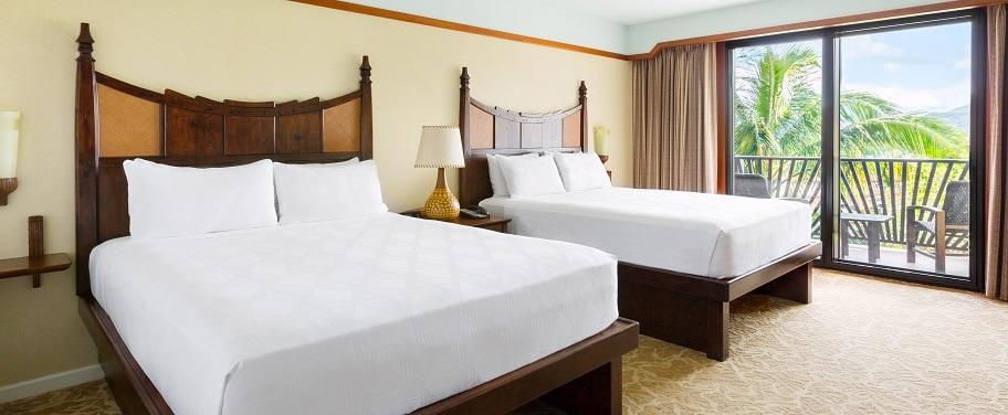 キングサイズのベッドとクイーンサイズのソファーベッドの向かい側に薄型テレビと 2 人用のテーブル、奥のバルコニーから見える景色