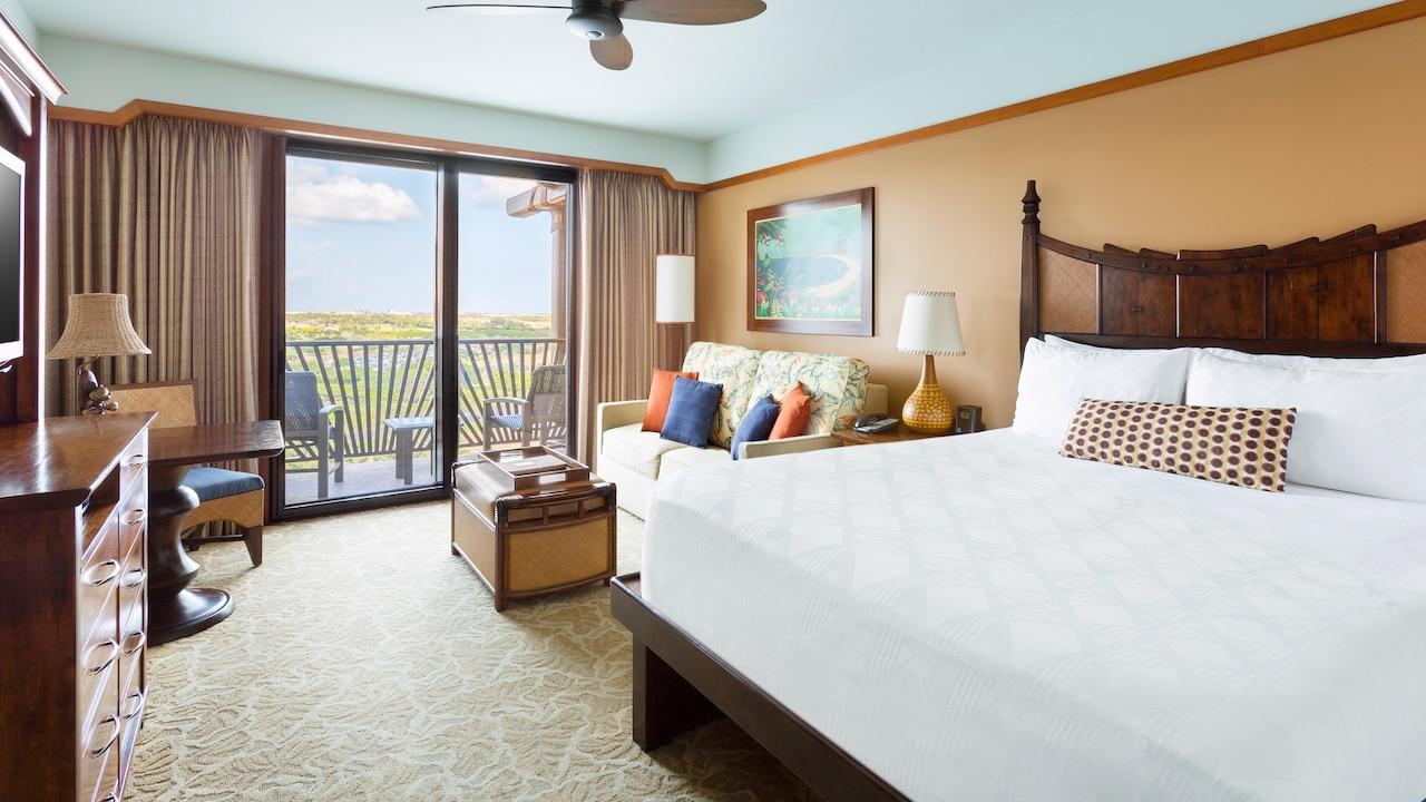 ベッド、カーペット、ソファベッド、テーブル、椅子、ランプ 2 個、カーテンが配されたお部屋
