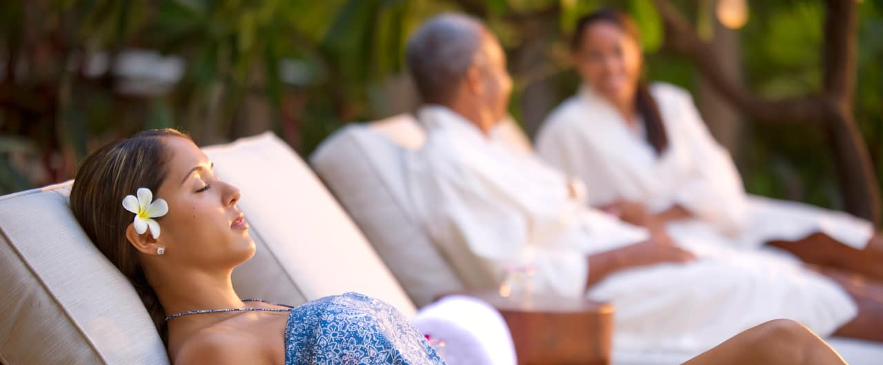 A woman lounging in the outdoor hydrotherapy garden at Laniwai – A Disney Spa