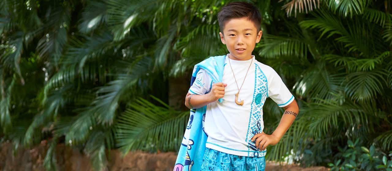 A boy with Hawaiian print board shorts and a fish hook necklace holds a towel over his shoulder