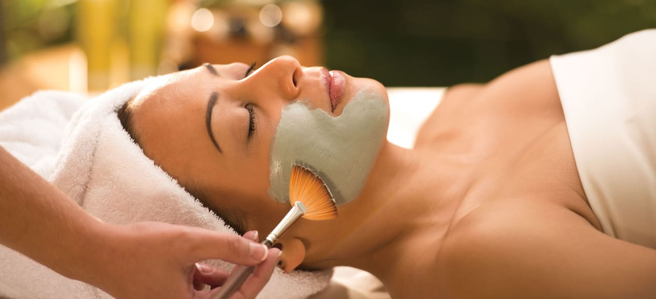 A woman lies with her hair wrapped in a towel as an aesthetician applies a facial mask with a brush