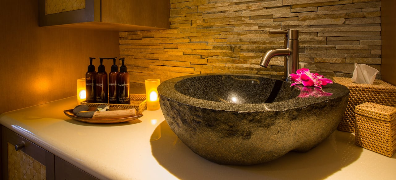 A basket of body lotion dispensers and 2 candles are set beside a polished granite wash basin