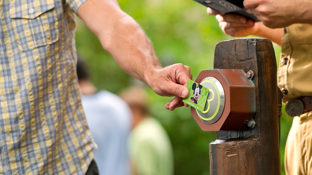 A Guest holds a card in front of a FastPass Plus scanner