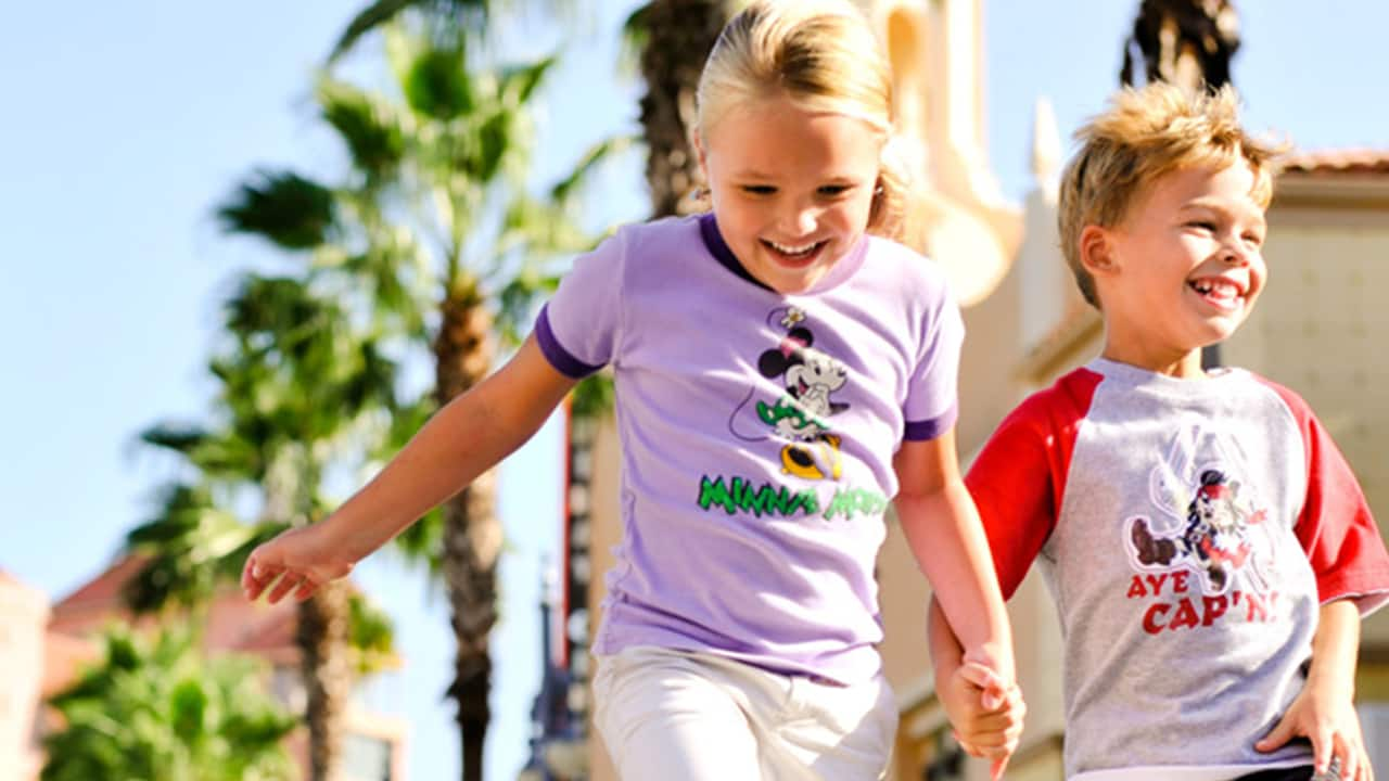 A young brother and sister run past palm trees, holding hands and smiling