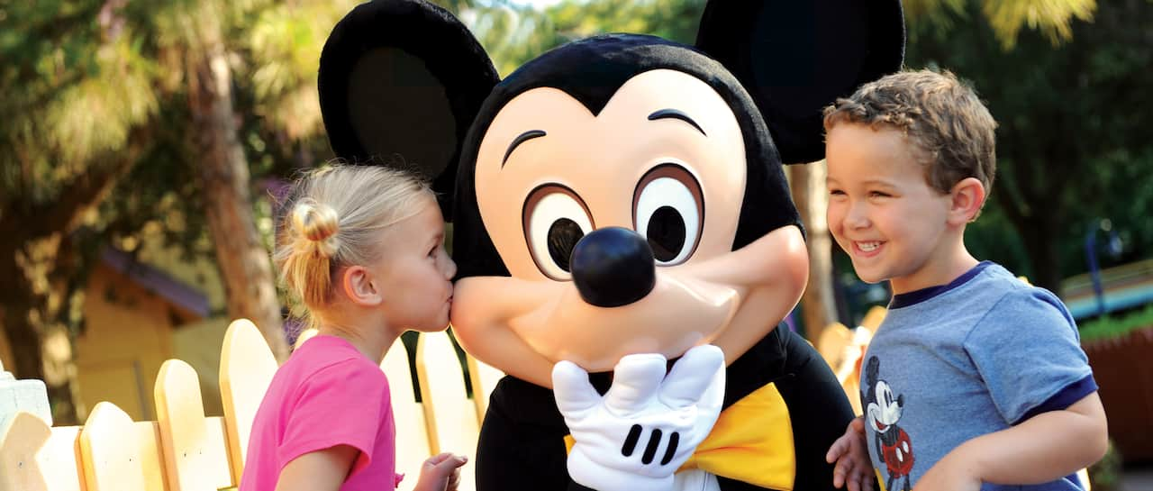 A little Guest kisses Mickey Mouse on the cheek as another little Guest looks on, smiling