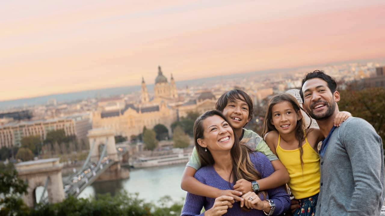 A family stands on a hill overlooking a suspension bridge over a river that leads into a city