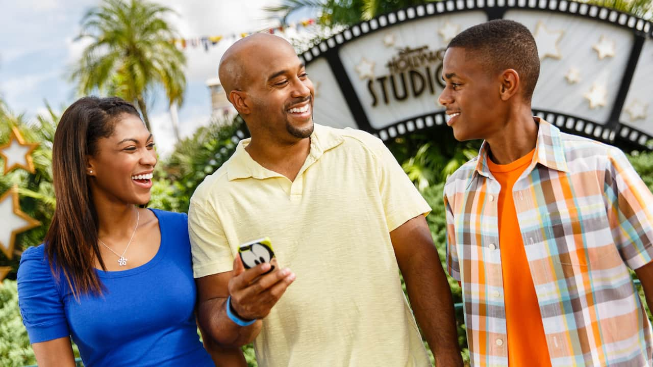 A family of 3 smiles at what is on the screen on a smartphone with a Goofy case