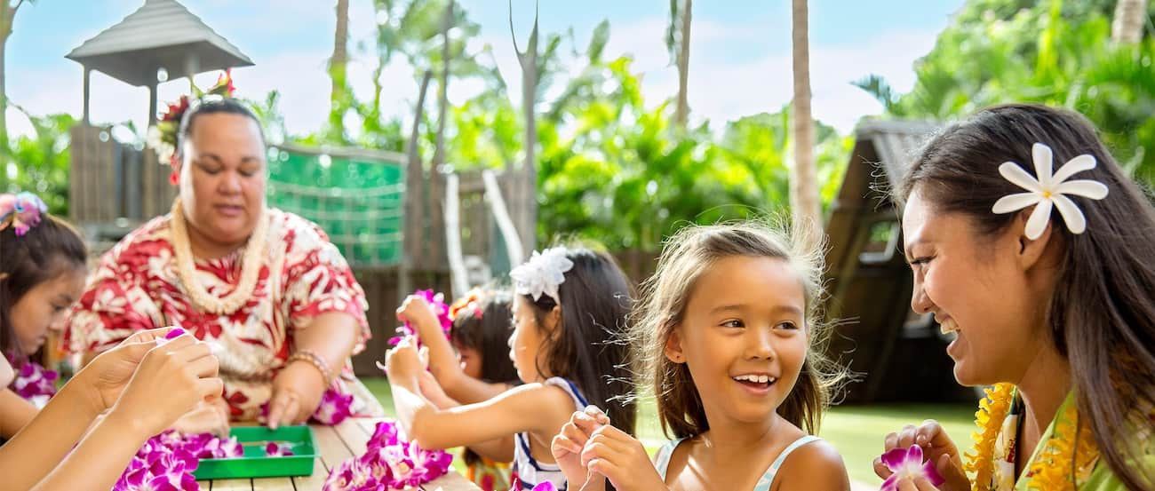 A Cast Member with a flower in her hair talks with a young girl during a lei-making activity at an outdoor table at Aunty's Beach House