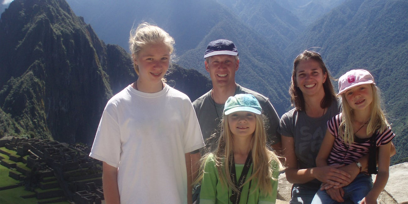 The Fimy family of five pose for a picture with the green mountains of Peru in the background