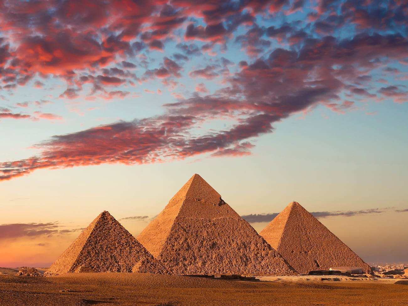 Three pyramids beneath a cloudy sky at dusk