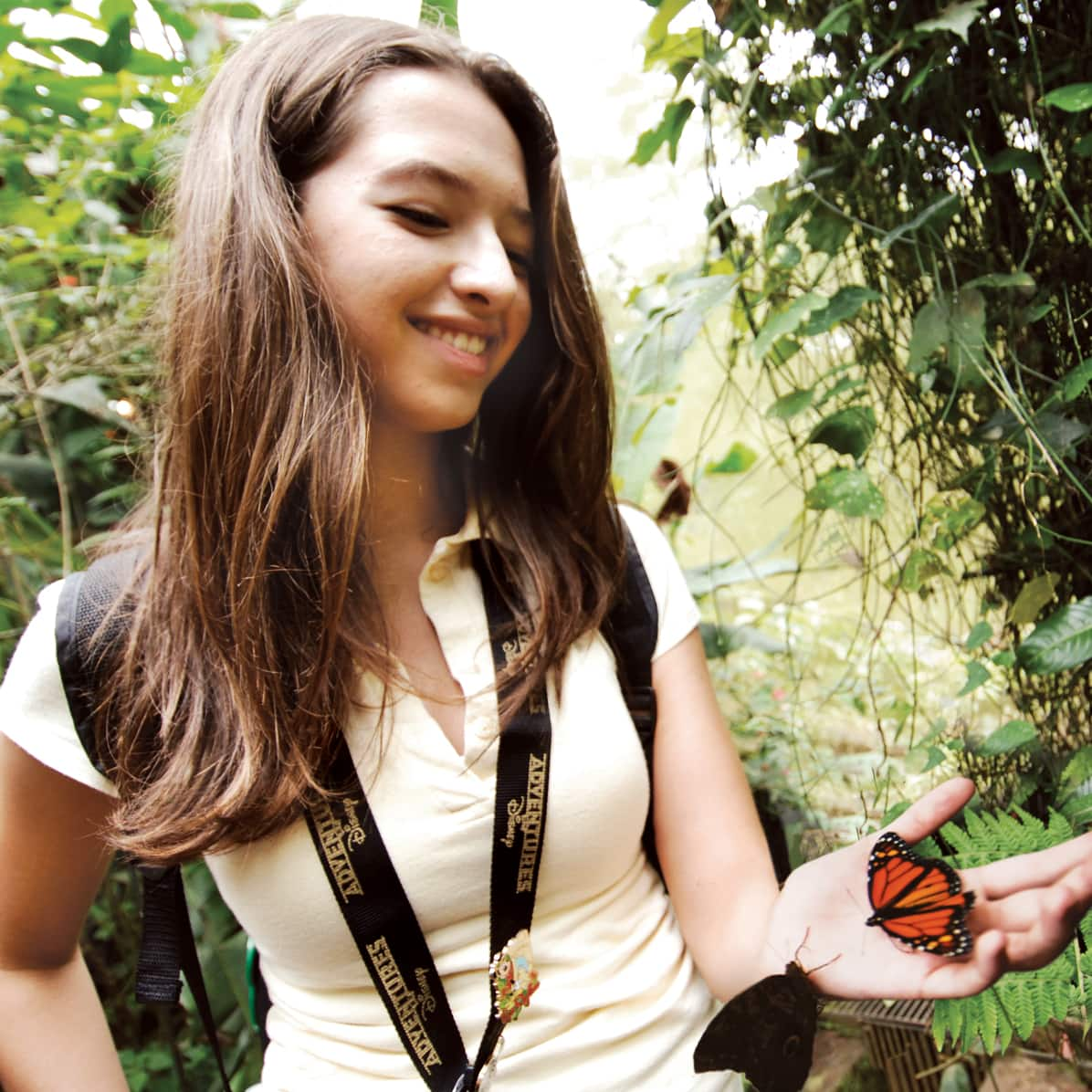 Two butterflies sit on the hand of a girl wearing an Adventures by Disney lanyard