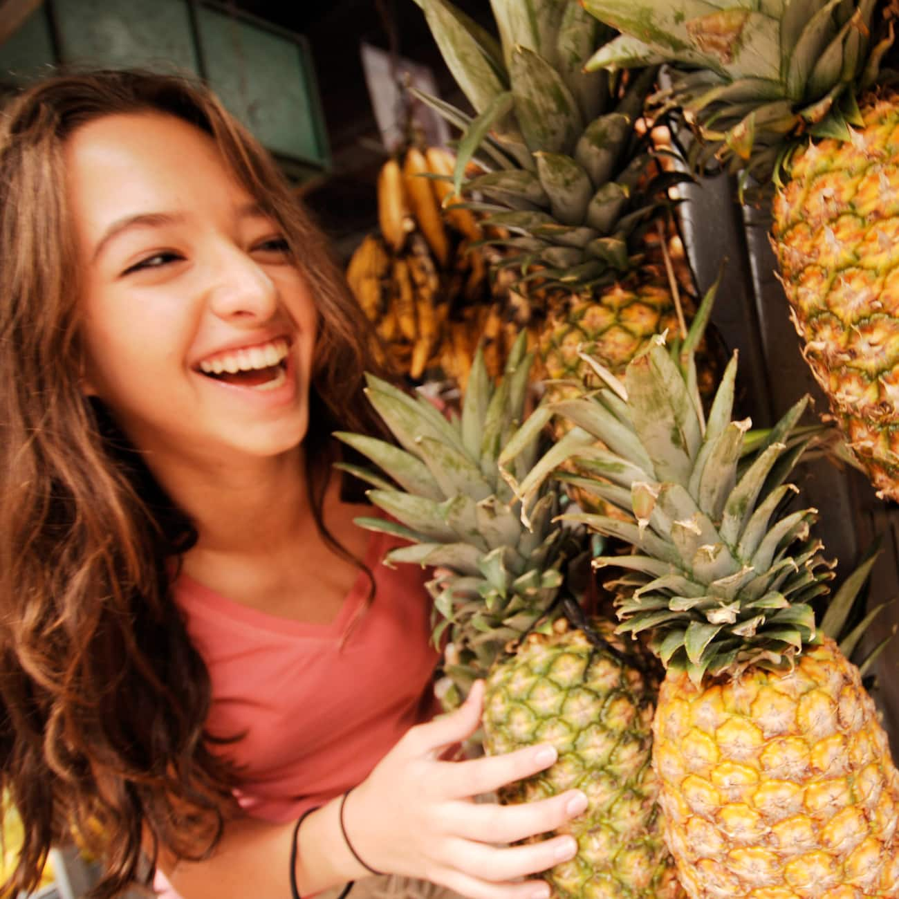 A smiling girl stands near a display of pineapples