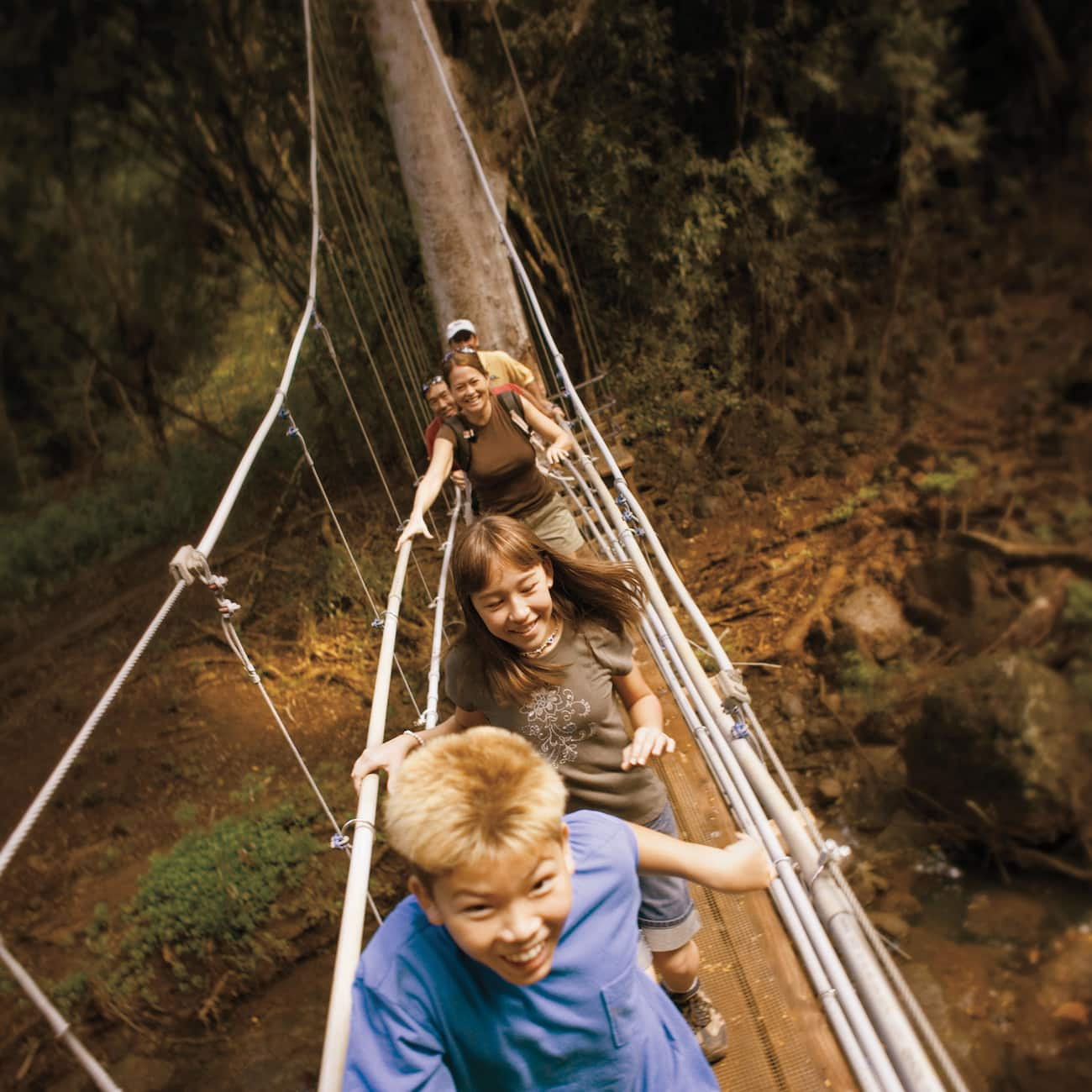 A group of Adventurers cross a hanging bridge above the rainforest in Costa Rica