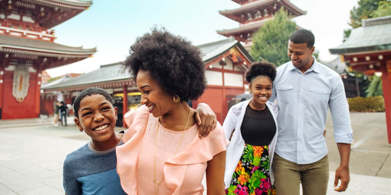 A family of 4 are all smiles as they walk in the courtyard of a Japanese temple