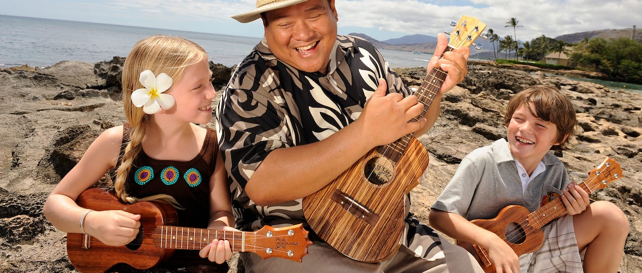 A girl, holding a small 'ukulele, watches a smiling man play the 'ukulele with ease