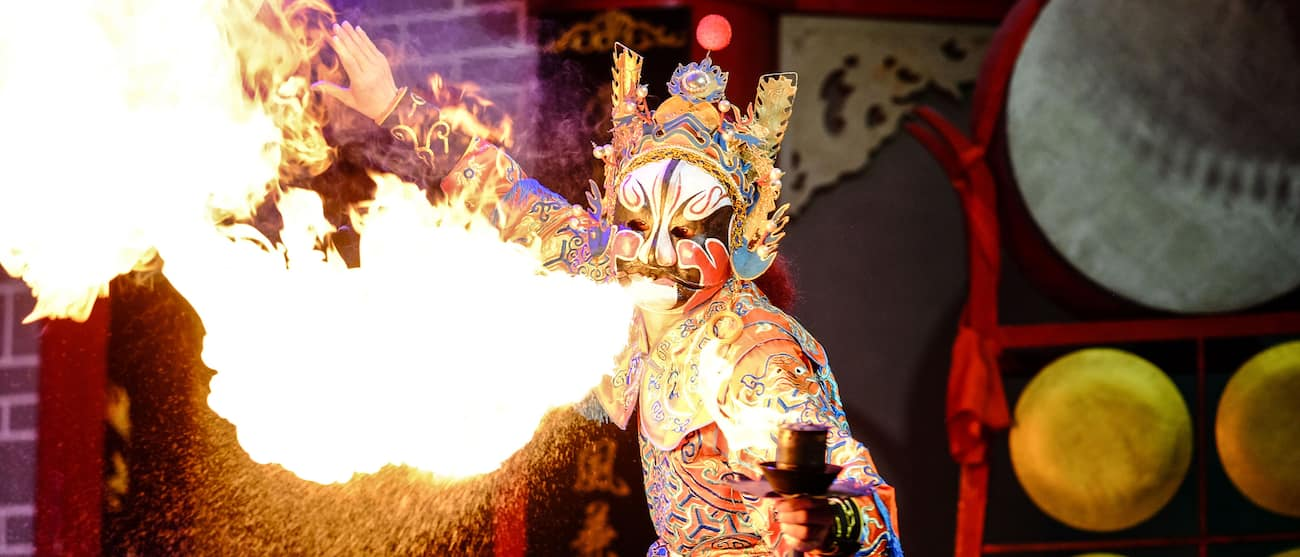 A performer in costume and mask breathes fire during a performance