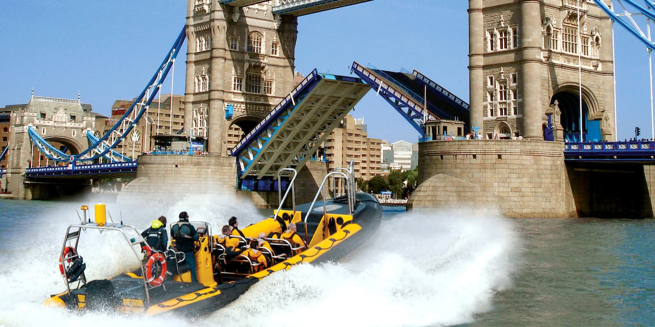 A speedboat races towards Tower Bridge on the Thames River