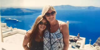 Marcy Ferruggia and her daughter pose for a picture with Santorini behind them.