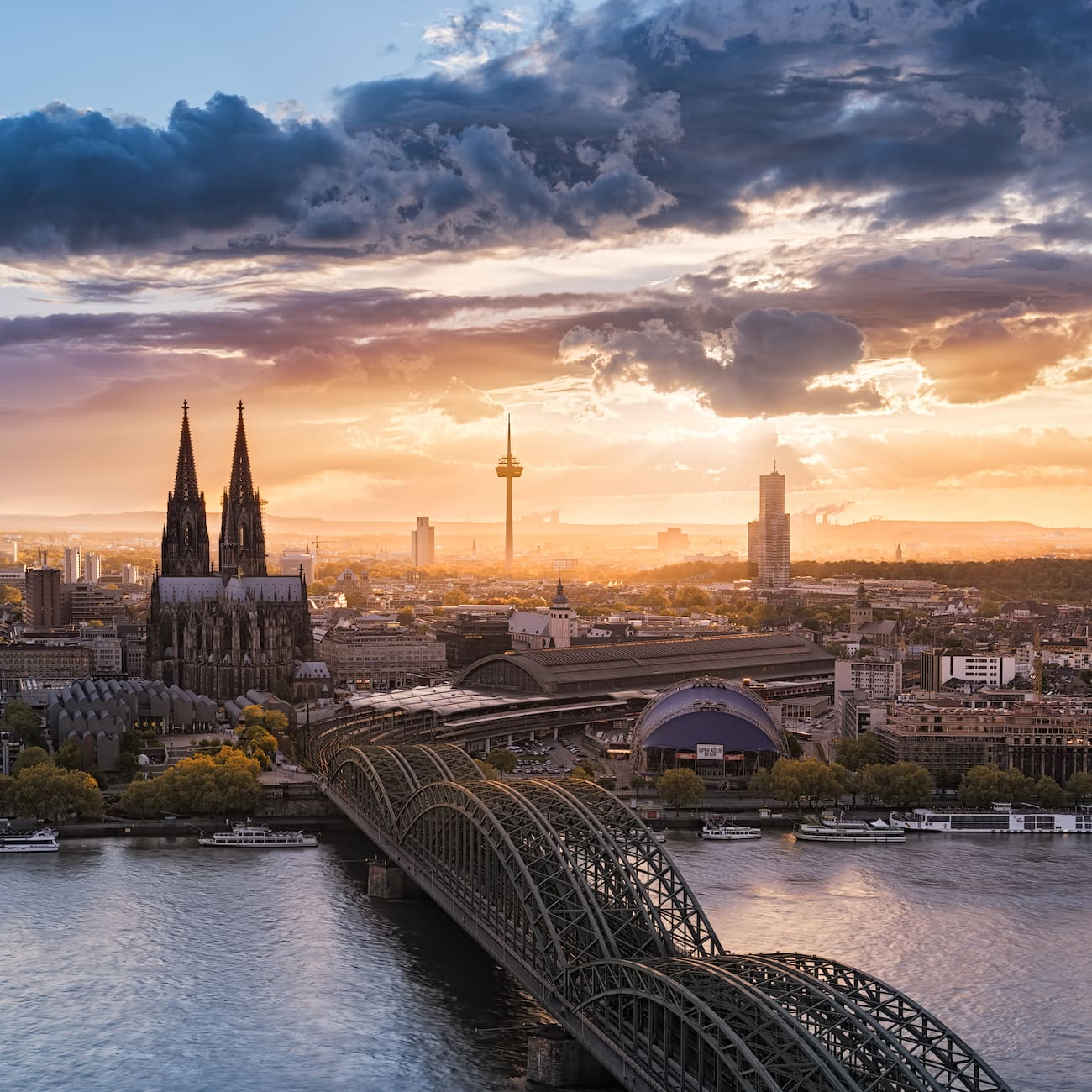 A city featuring a church with spires, skyscrapers and a covered bridge that spans the Rhine River