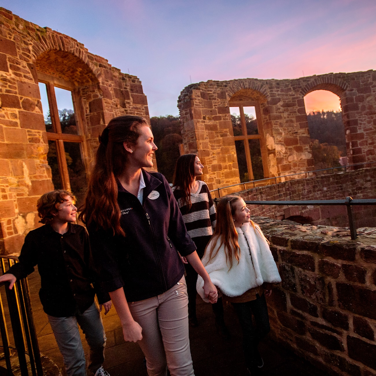 A female Adventure Guide leads a group of 3 people through the windows of the remains of a stone structure at dusk