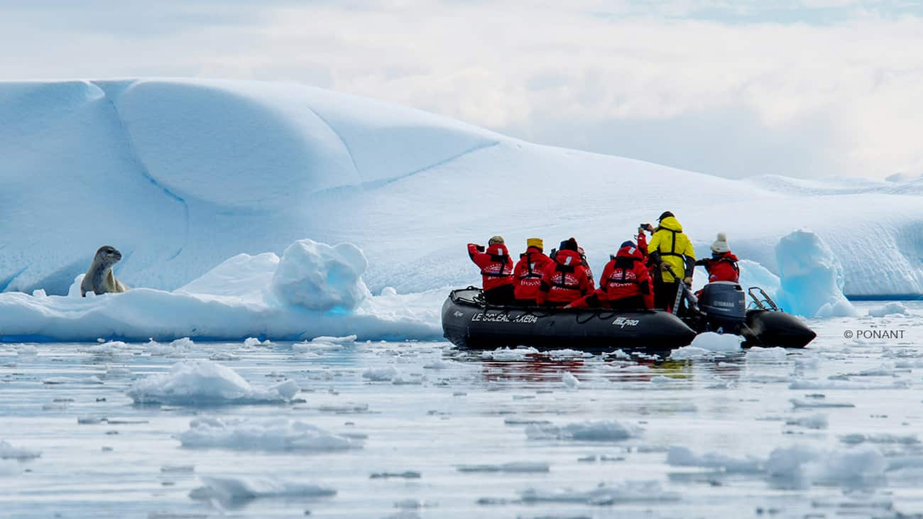 Seven people clad in parkas on a zodiac boat take pictures of a seal on an iceberg