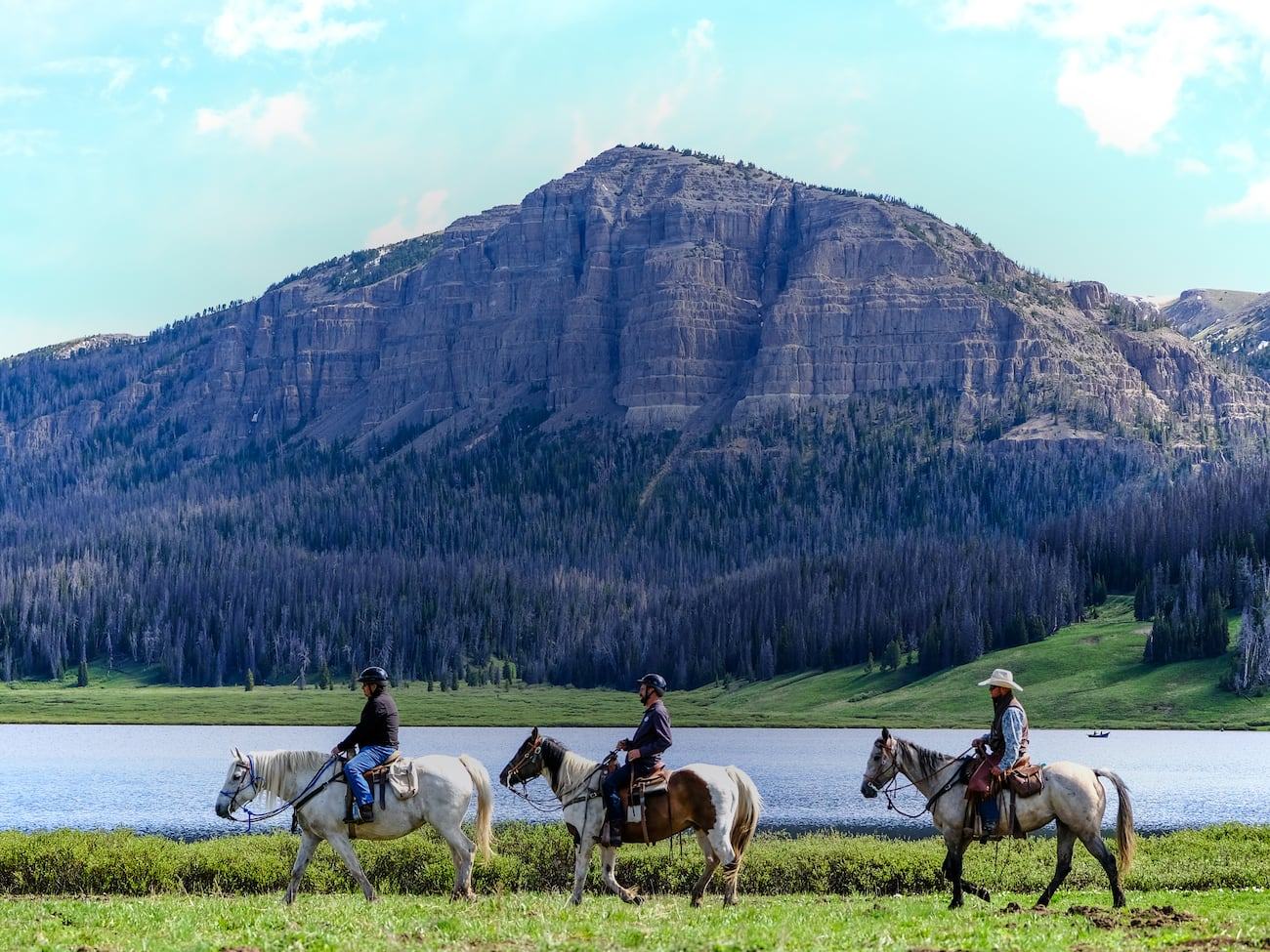 Three people ride horses near a lake across from a mountain with a forest at its base