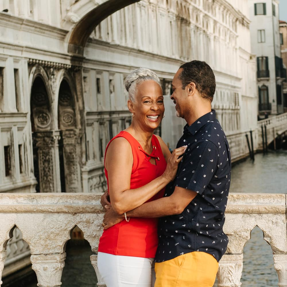 A smiling couple embracing on a pedestrian bridge in Venice