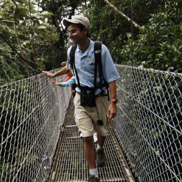 An Adventure Guide leads a family over a pedestrian bridge surrounded by trees