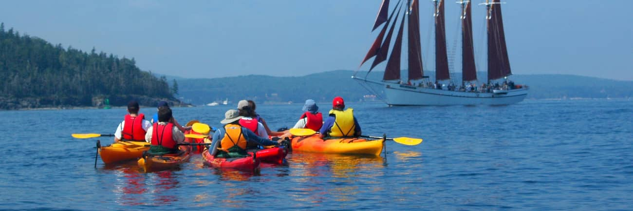 A group of kayakers on 2-person kayaks in the water near a four masted sailing ship