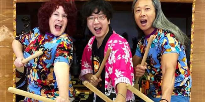 Three people with mouths agape hold drum sticks and pose by a large taiko drum