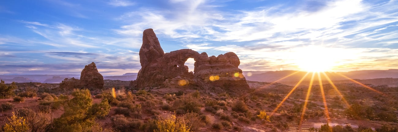 A sandstone arch in Arches National Park at sunrise