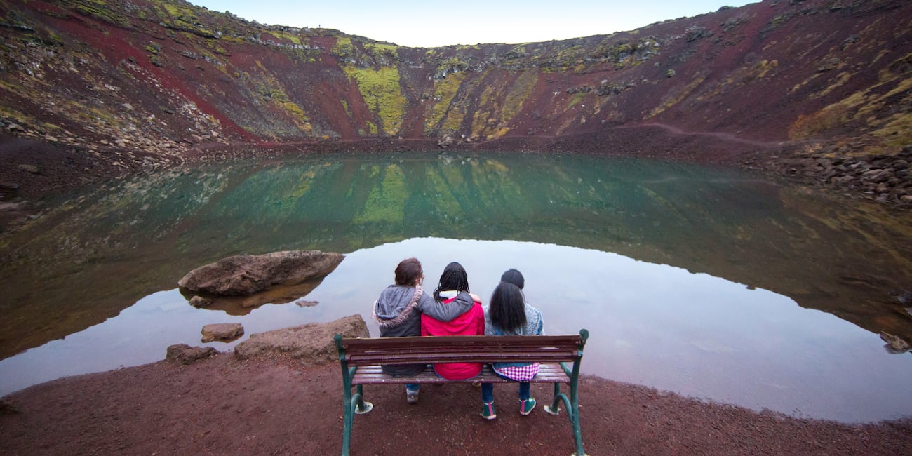 Three girls sitting on a bench overlooking a volcanic crater lake in Iceland