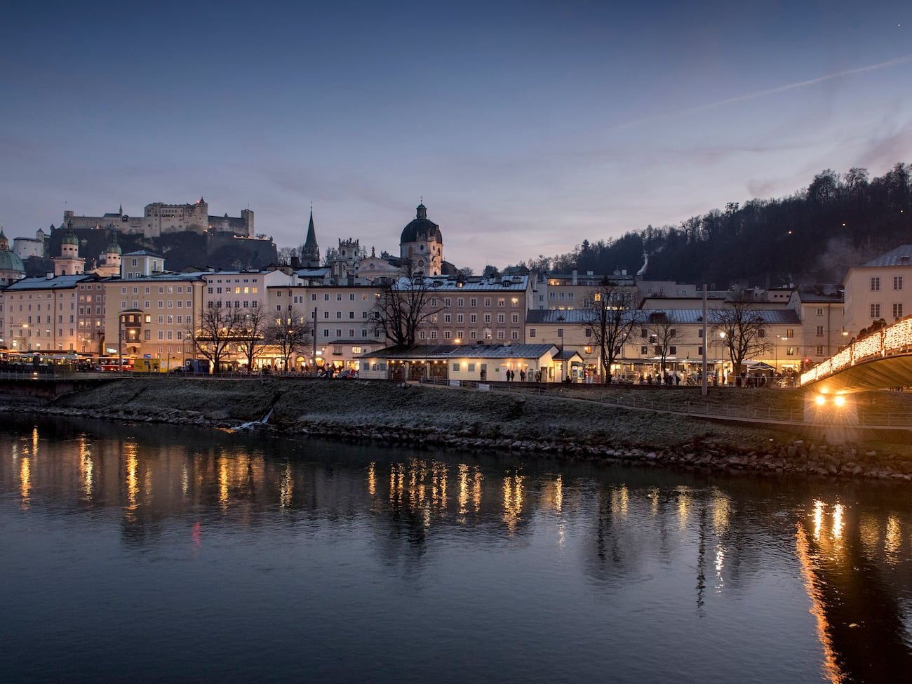 The city of Salzburg, Austria on the bank of a river spanned by a bridge lit up at dusk