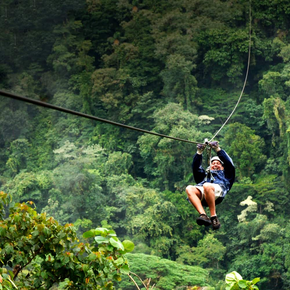 A man is all smiles as he zip lines above the treetops of a lush forest